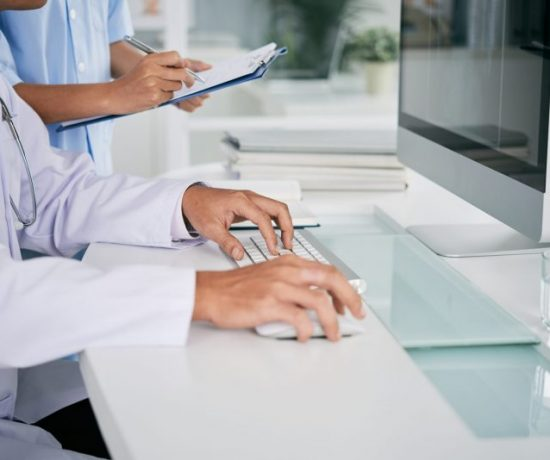 Cropped image of doctor working on computer at his table